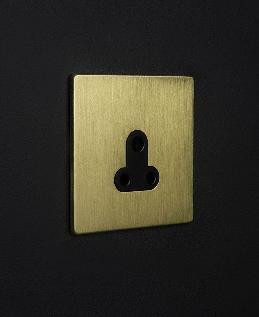 gold and black three pin socket against black background
