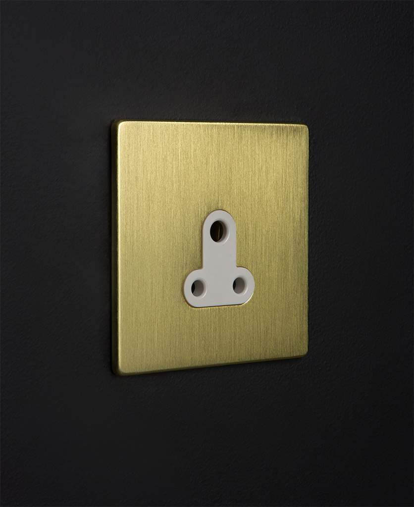 gold and white three pin socket against black background