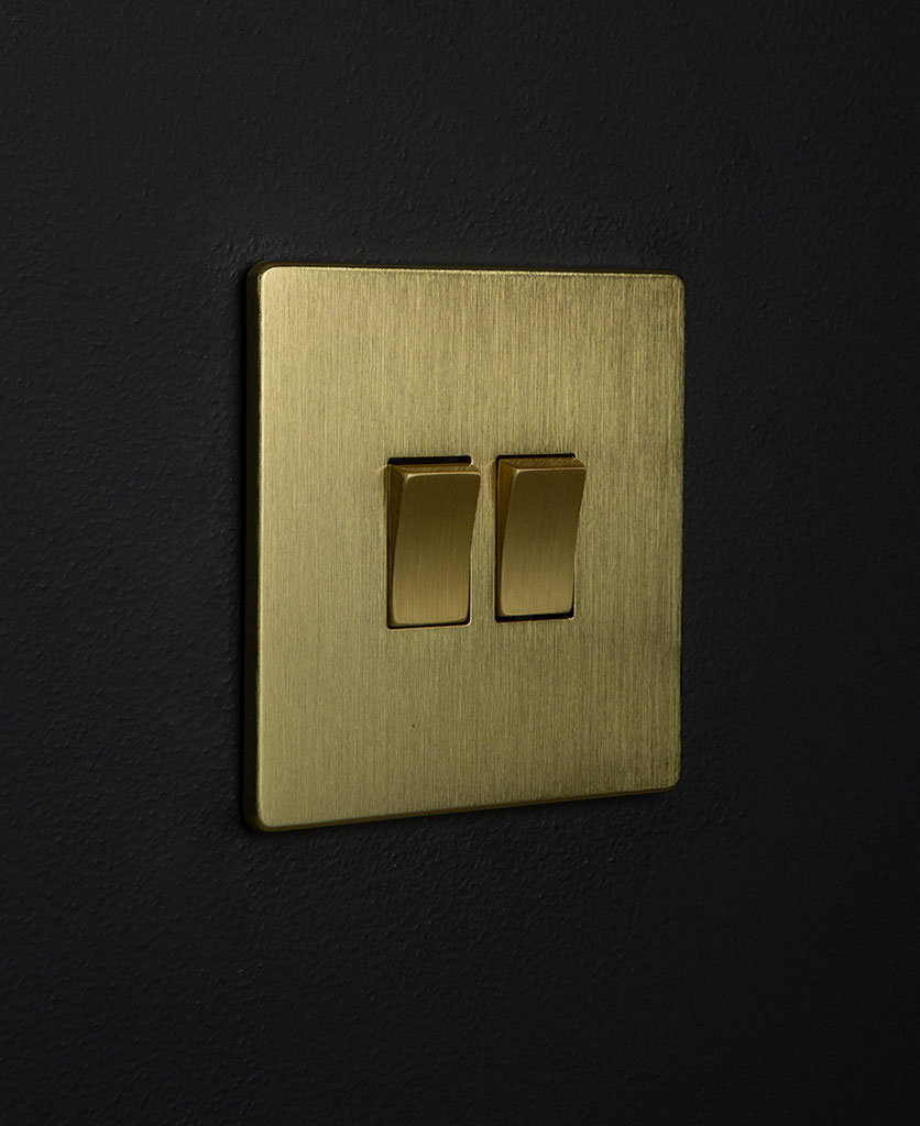 gold double light switch with gold rocker detailing on a black wall