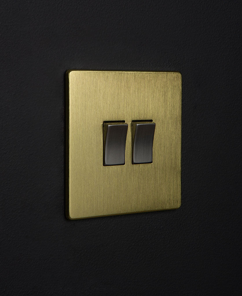 gold and silver double rocler switch against black background
