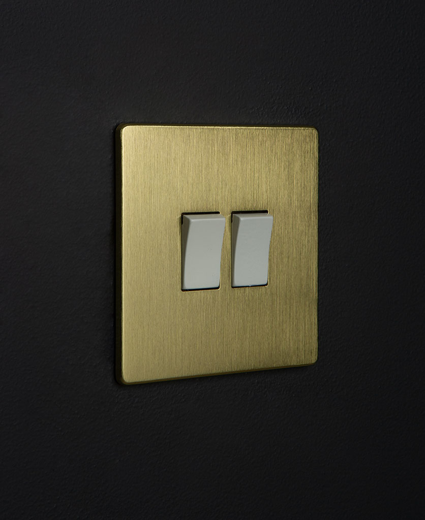 gold and white double rocker switch againstblack background
