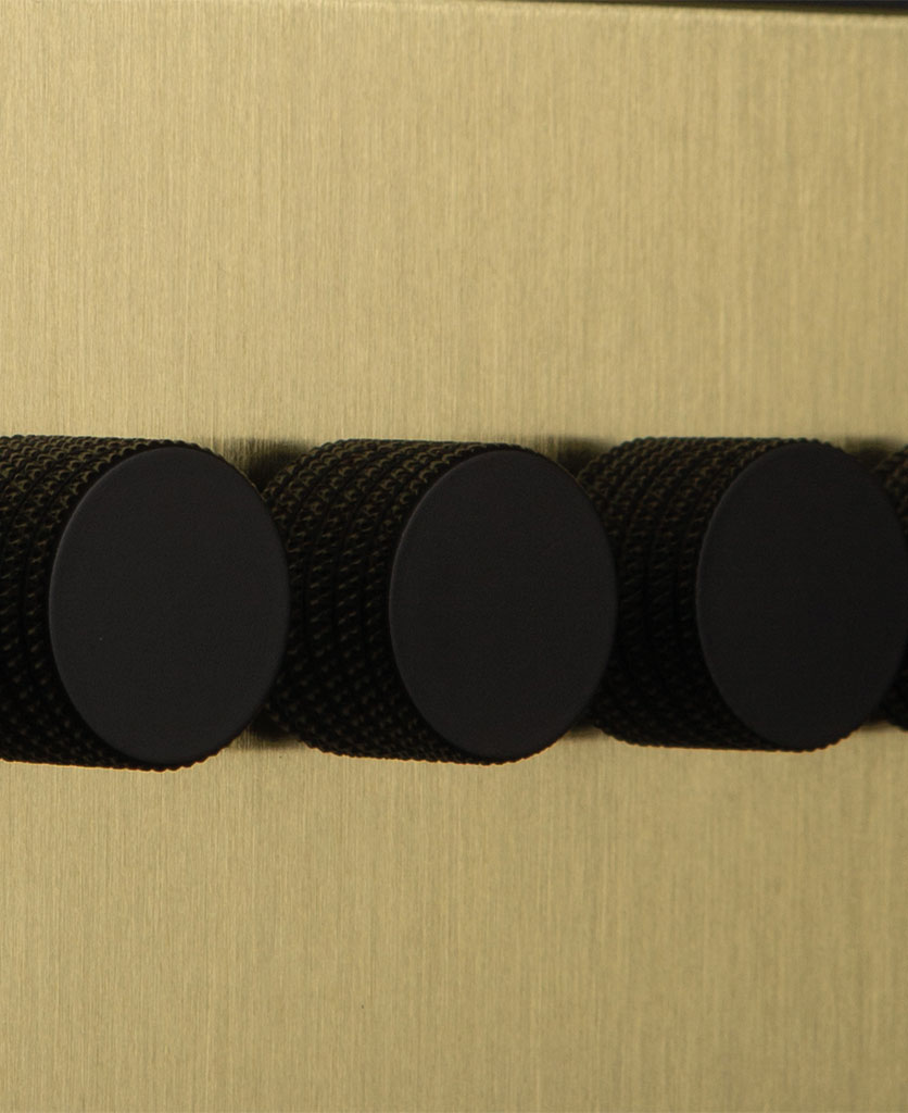 closeup of gold & black quad dimmer against black background