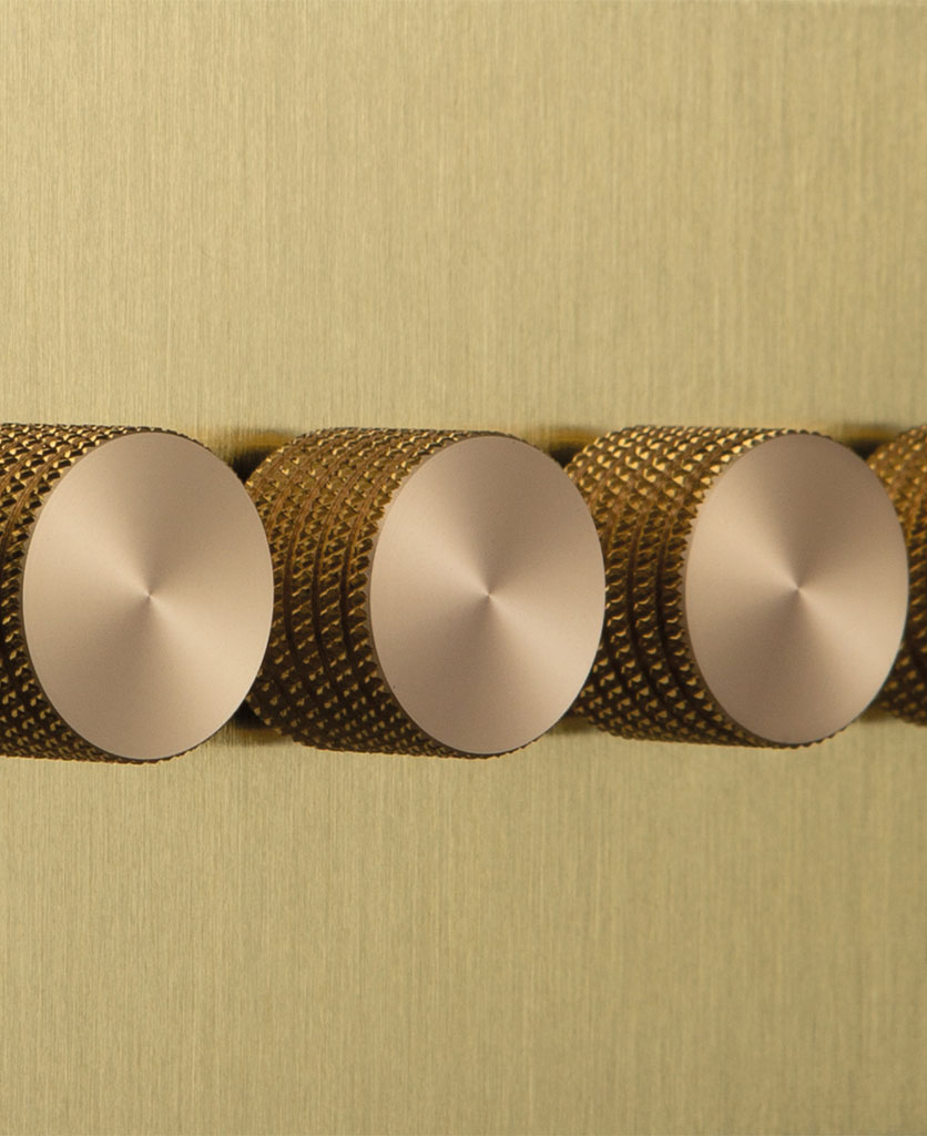 closeup of gold & gold quad dimmer against black background