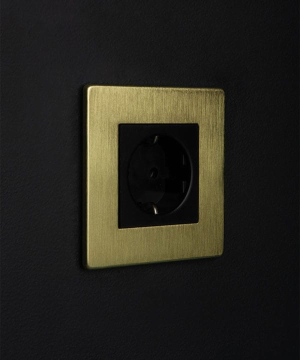 gold and black single schuko socket against black background