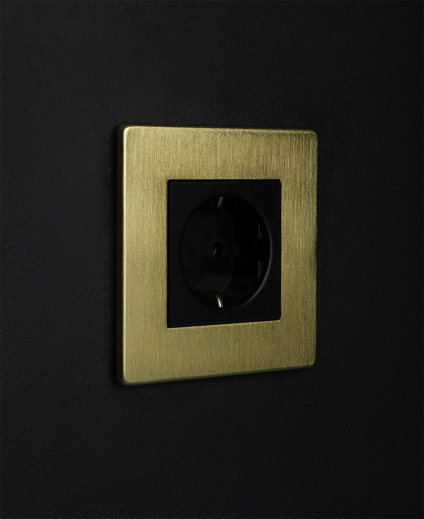 gold and black single schuko socket against black background