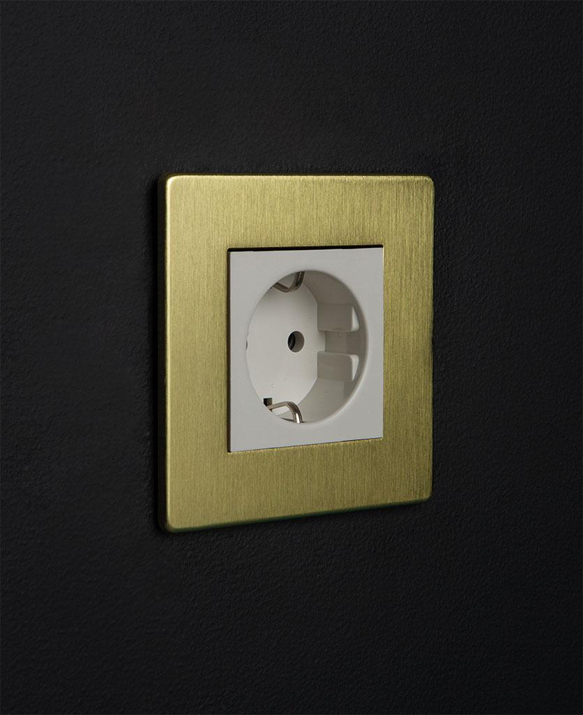 gold and white single schuko socket against black background