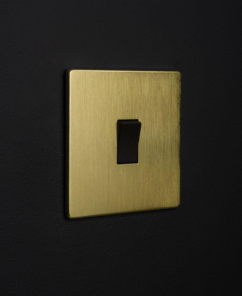gold rocker light switch with single black rocker detail on a black wall