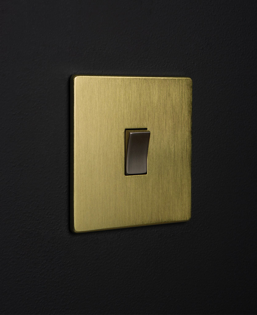 gold & silver single rocker against black wall