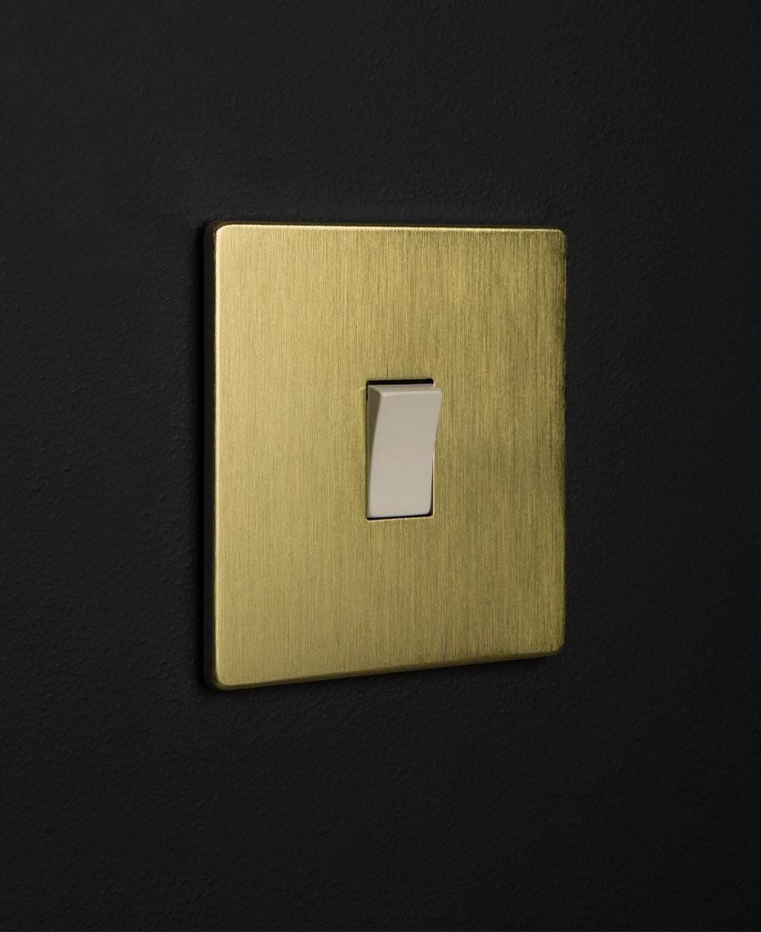 gold & white single rocker against black wall