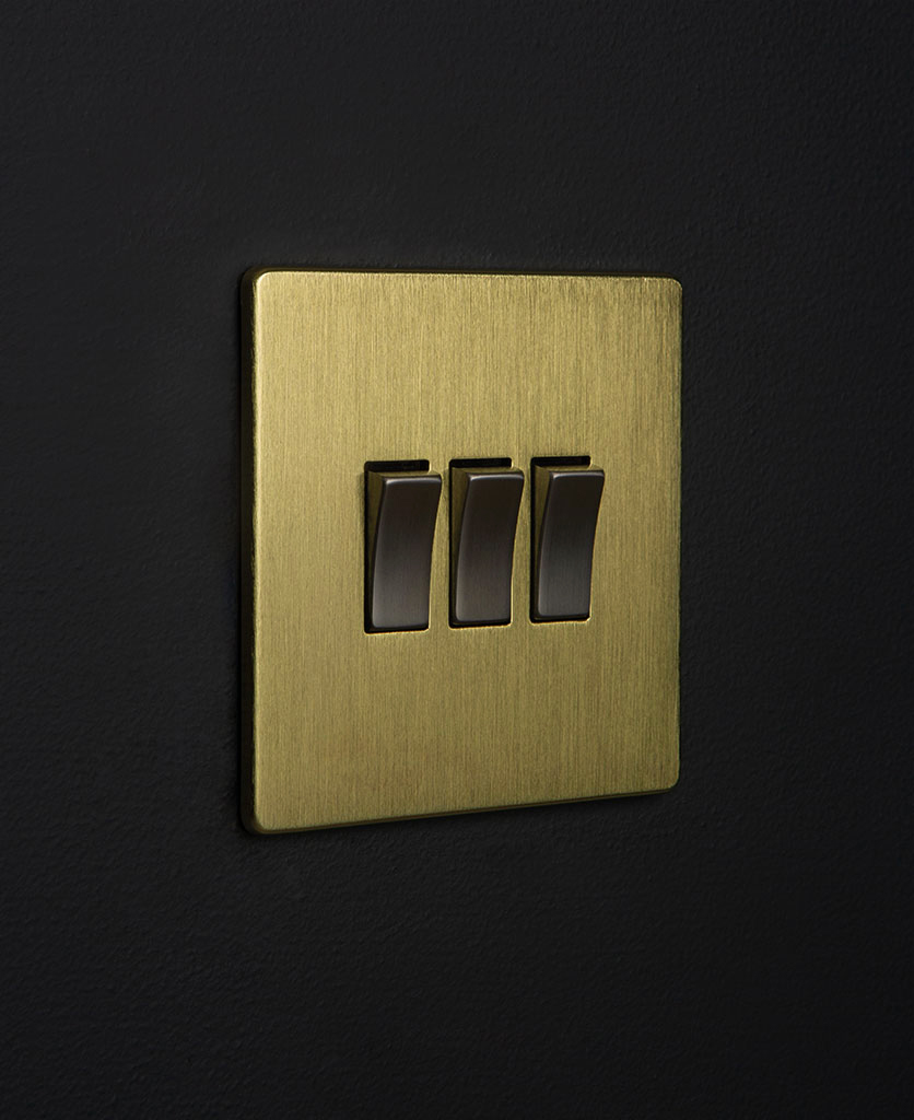 gold triple light switch with contrasting silver triple rocker detailing on a black wall