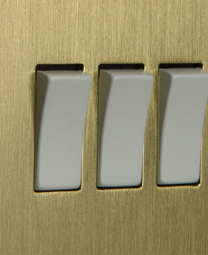 closeup of gold and white triple rocker switch
