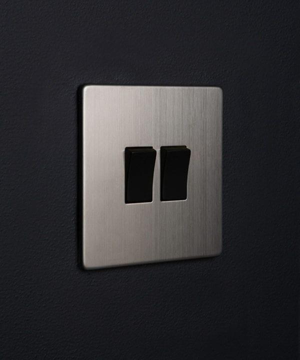 silver double light switch rocker with double black rocker detail on a black wall