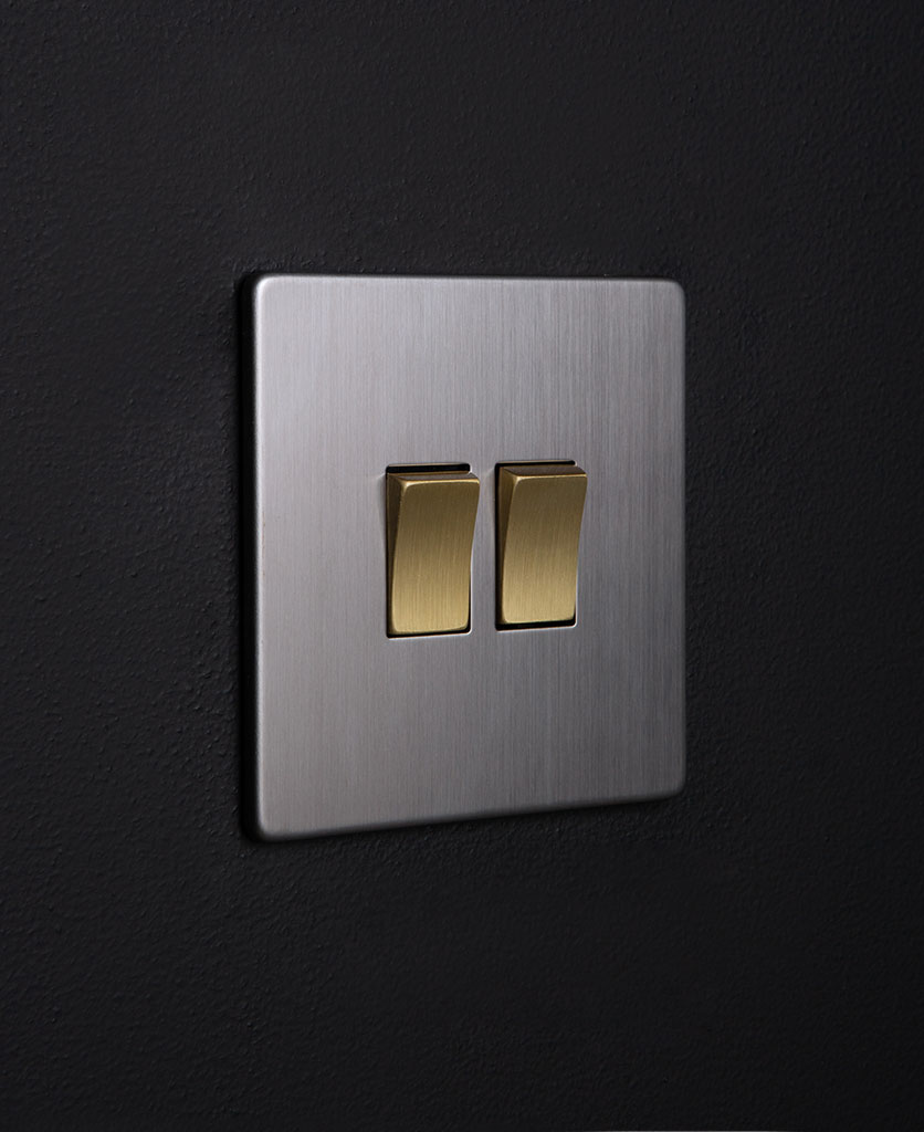 silver double light switch rocker with double gold rocker detail on a black wall