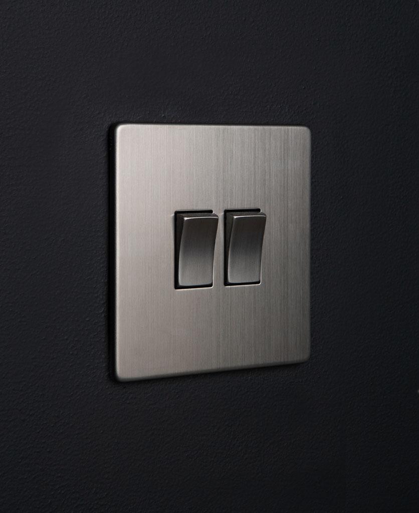 silver double light switch rocker with double silver rocker detail on a black wall