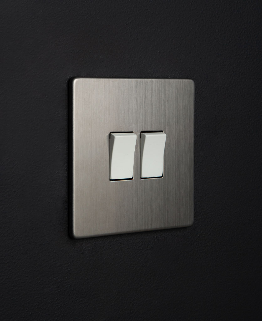 silver double light switch rocker with double white rocker detail on a black wall