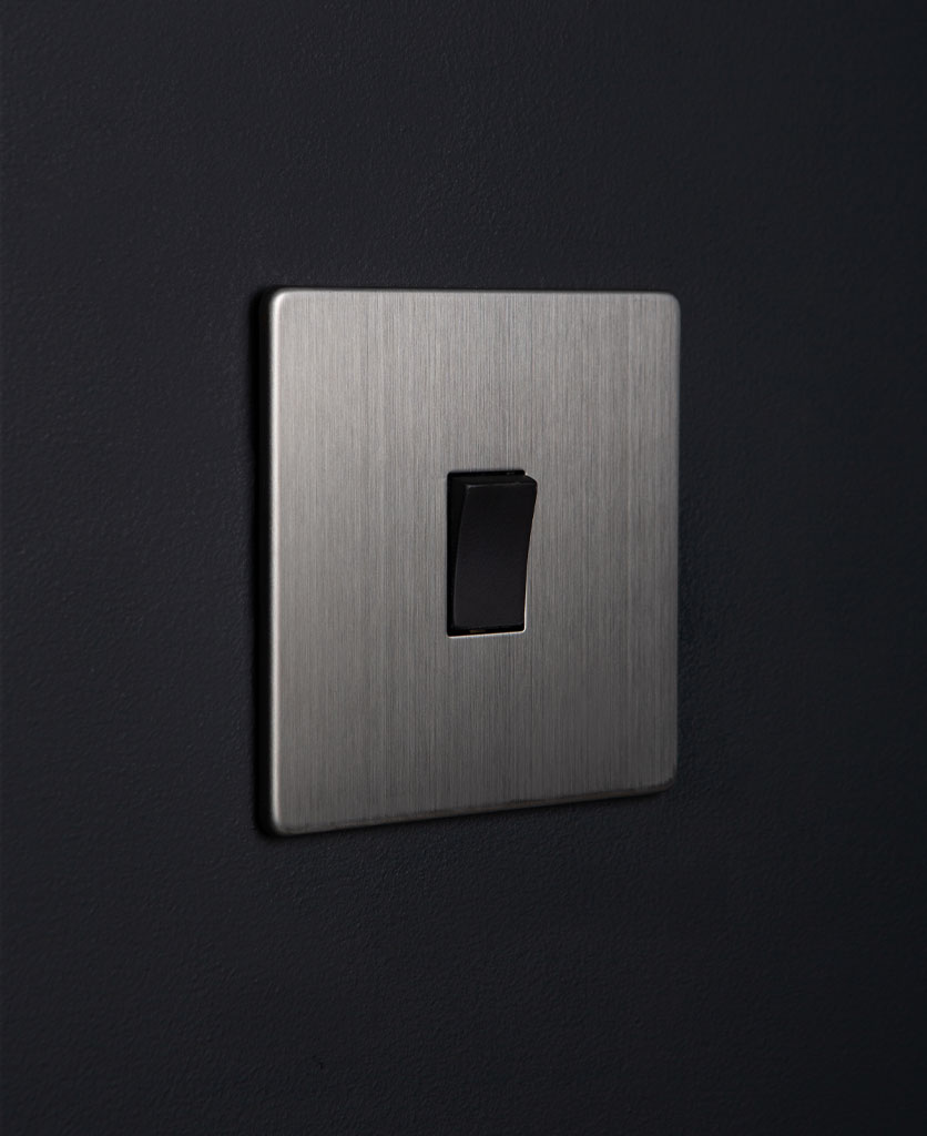 silver rocker switch with black single rocker detail on a black wall