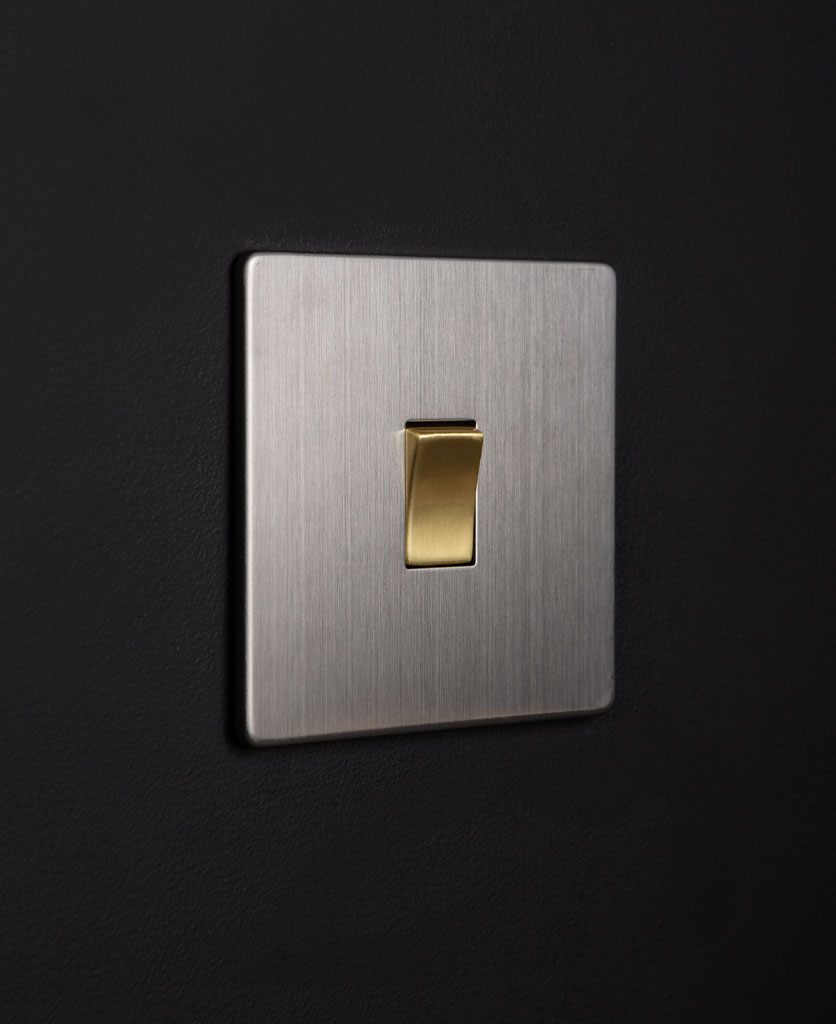 silver rocker switch with gold single rocker detail on a black wall