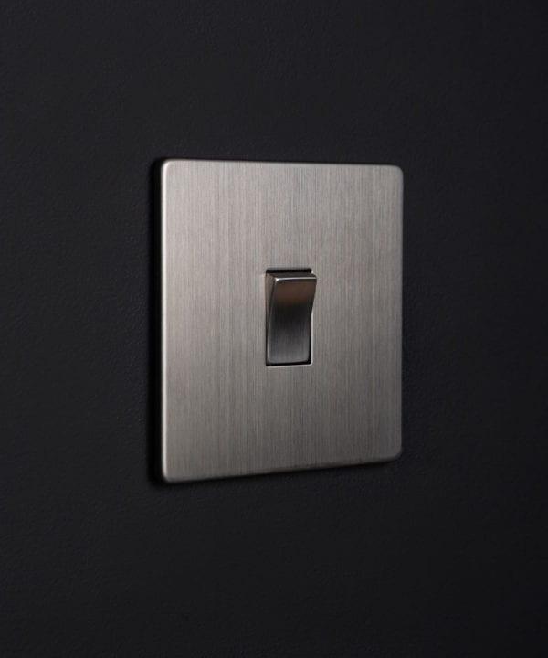 silver rocker switch with silver single rocker detail on a black wall