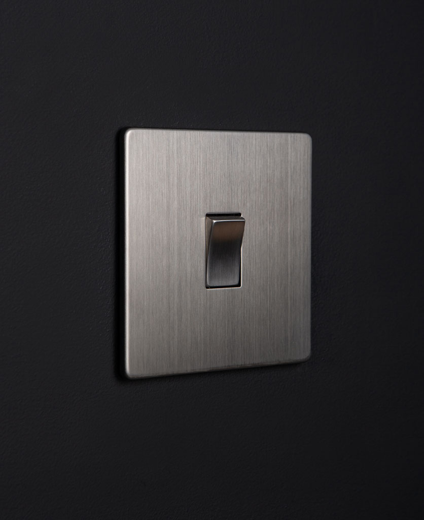 silver rocker switch with silver single rocker detail on a black wall