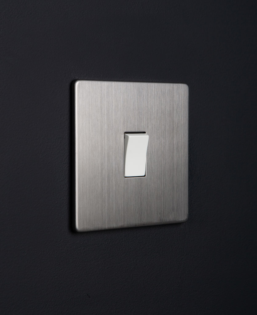 silver rocker switch with white single rocker detail on a black wall