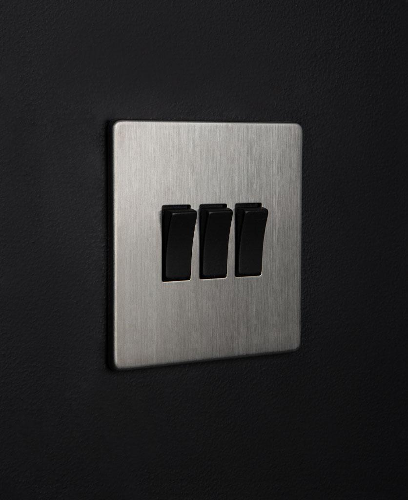 silver 3 gang light switch with triple black rocker detail on a black wall