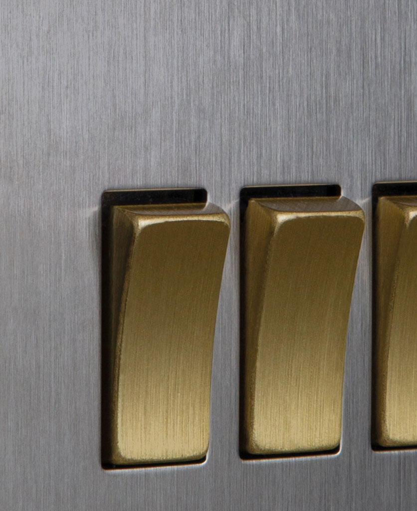 closeup of silver and gold triple rocker switch