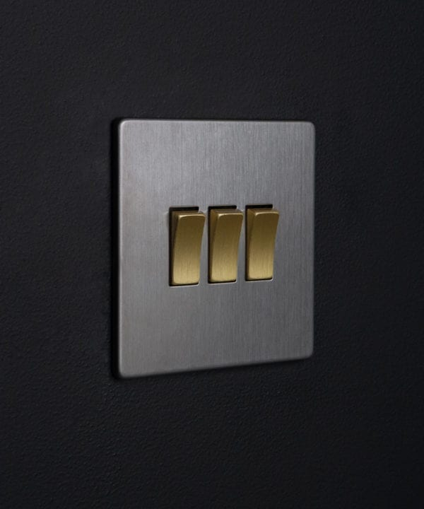 silver 3 gang light switch with triple gold rocker detail on a black wall