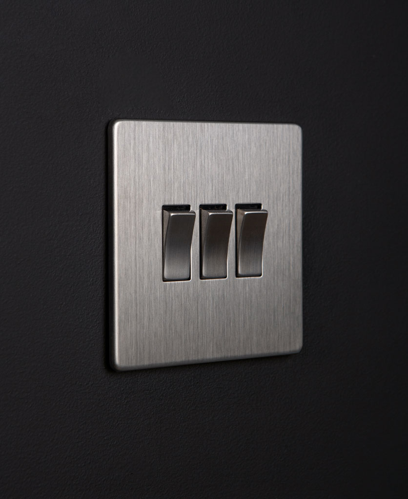 silver 3 gang light switch with triple silver rocker detail on a black wall