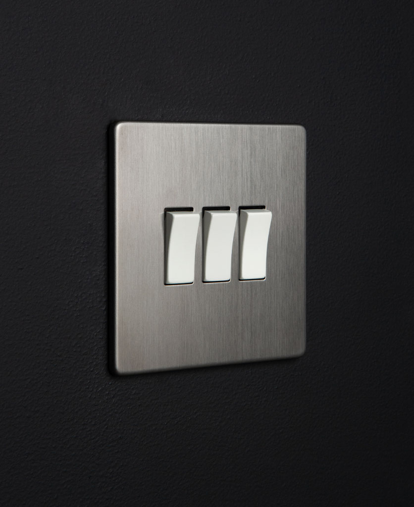 silver 3 gang light switch with triple white rocker detail on a black wall