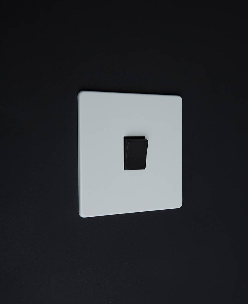 white electrical light switch with single black rocker detail on a black wall