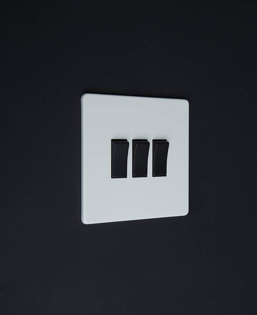 3 gang white rocker switch with black triple rocker detailing on a black wall