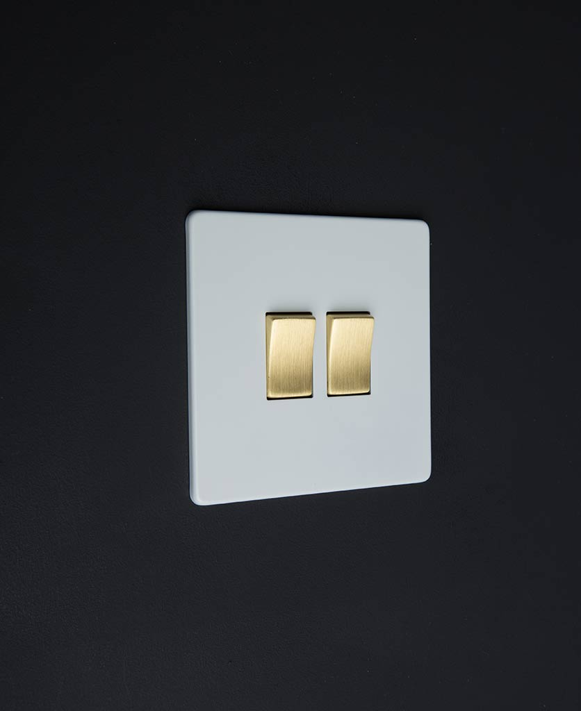 white & gold double rocker switch against black background