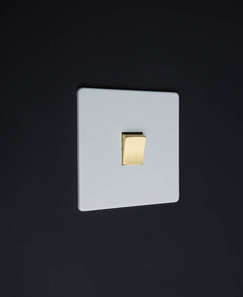 white electrical light switch with single gold rocker detail on a black wall