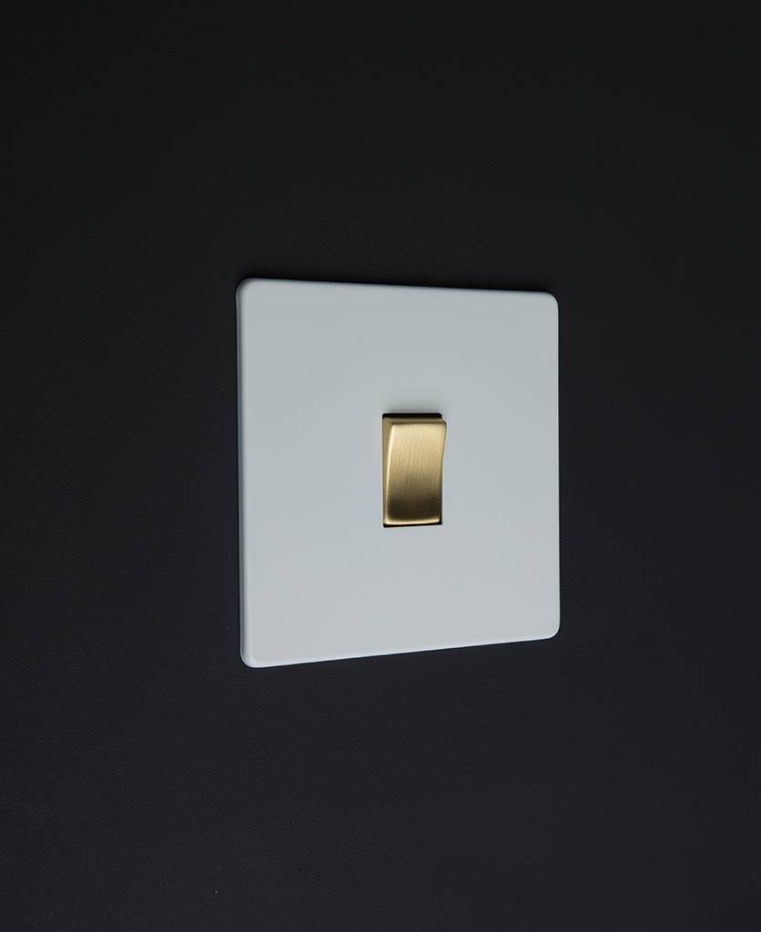 white & gold single rocker switch against black background