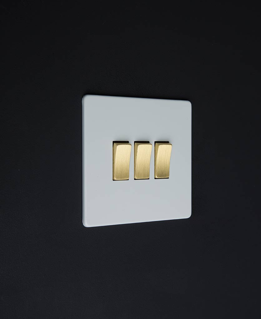 3 gang white rocker switch with gold triple rocker detailing on a black wall