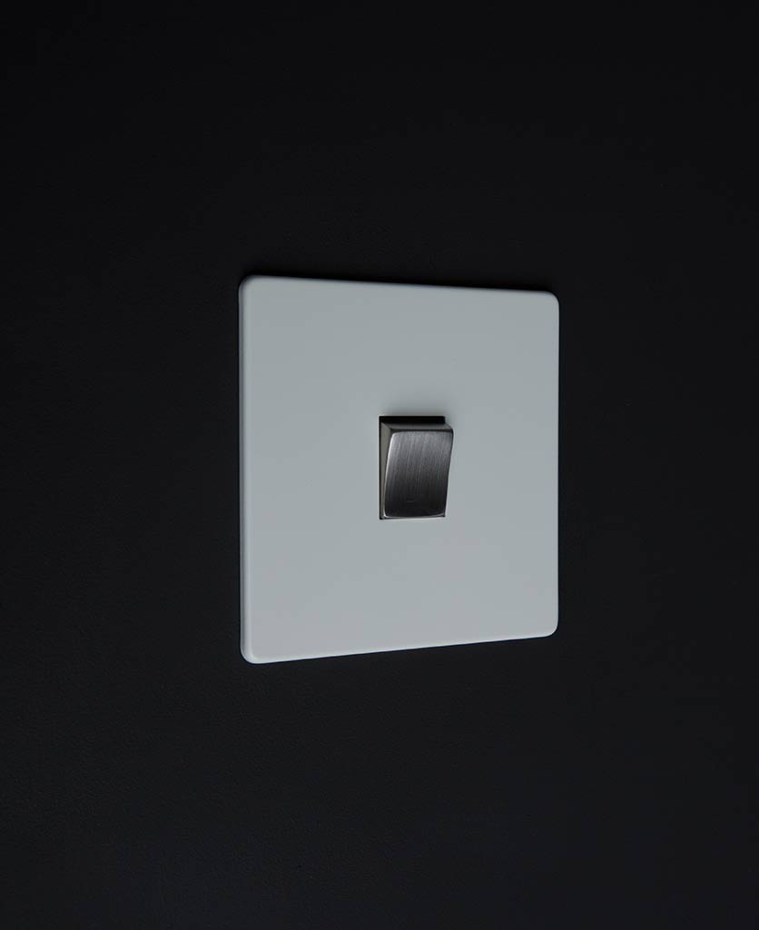 white electrical light switch with single silver rocker detail on a black wall