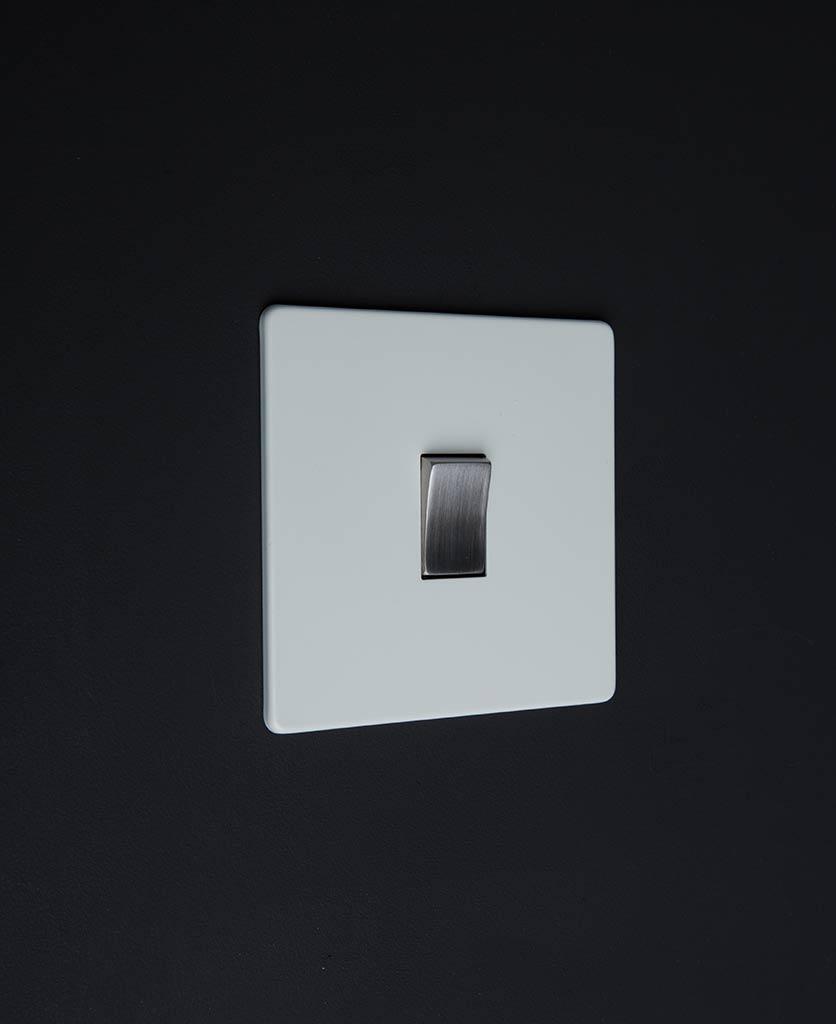 white & silver single rocker switch against black background