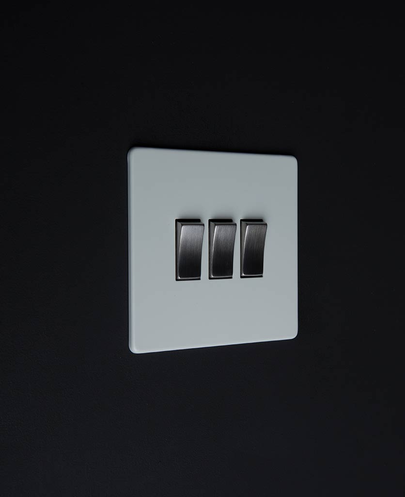 3 gang white rocker switch with silver triple rocker detailing on a black wall