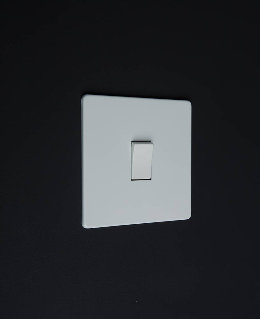 white & white single rocker switch against black background