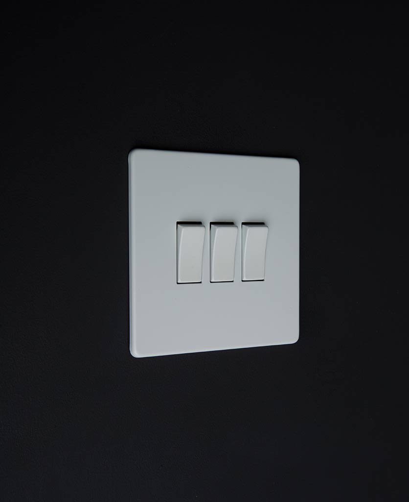 3 gang white rocker switch with white triple rocker detailing on a black wall
