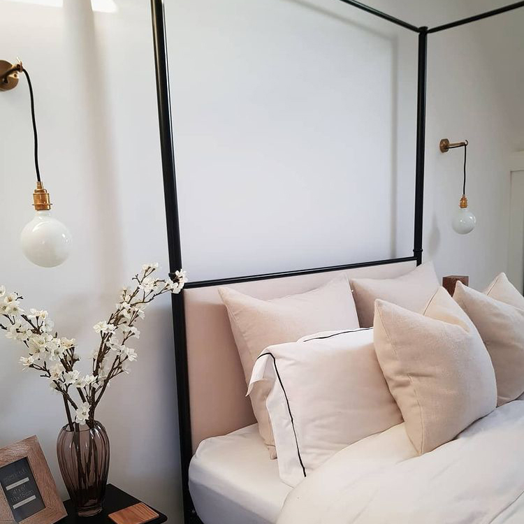 ANGLER brass wall lamp on either side of a four poster bed in a white bedroom