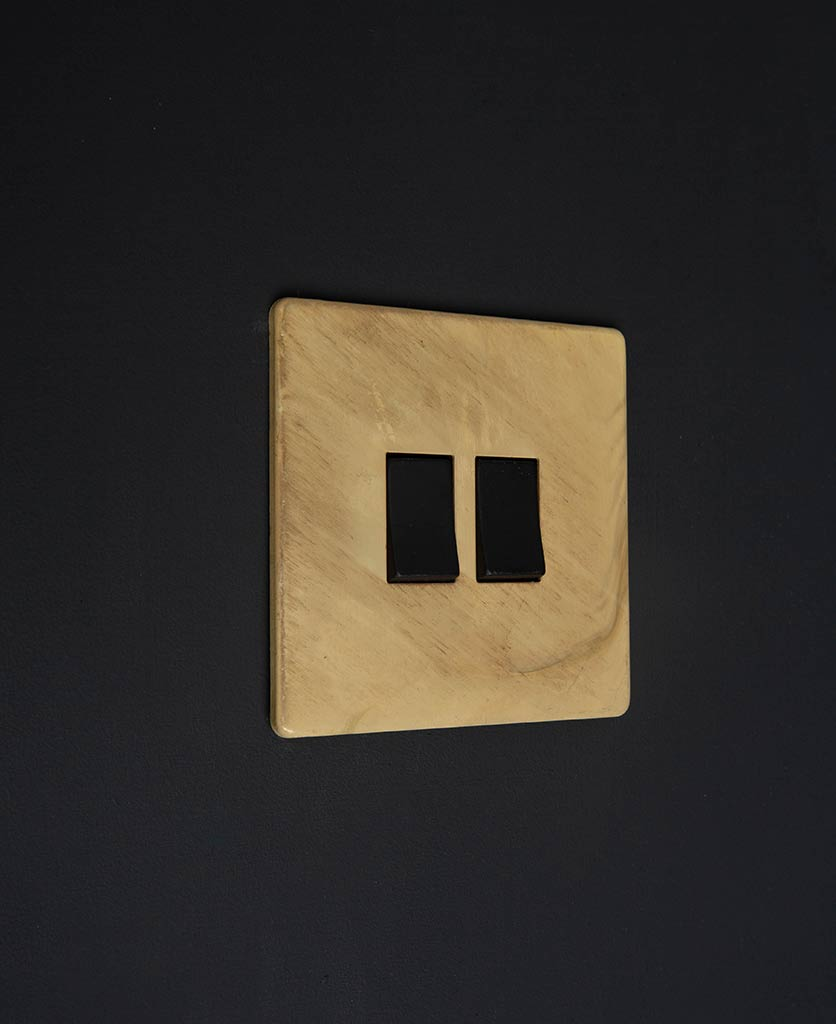 smoked gold 2 gang light switch with double black rocker detailing on a black wall