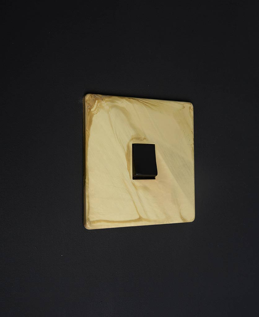 smoked gold single LED rocker switch with matt gold plate and single black rocker detail on a black wall