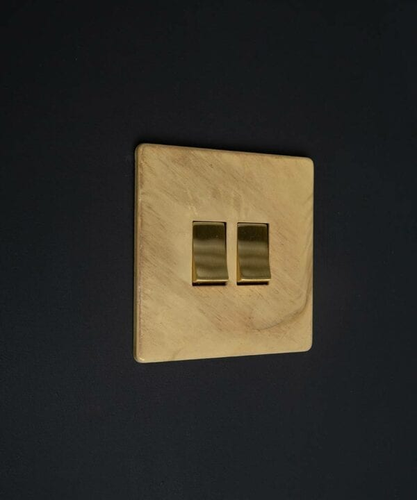 smoked gold 2 gang light switch with double gold rocker detailing on a black wall
