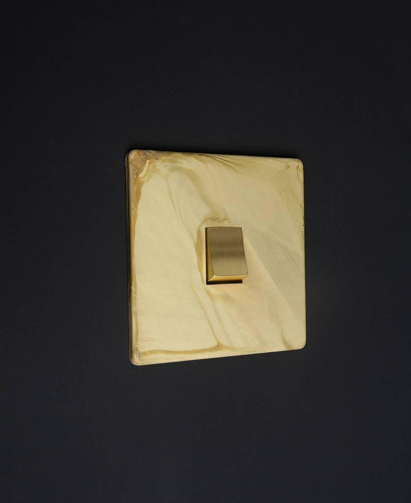 smoked gold single LED rocker switch with matt gold plate and single gold rocker detail against black wall