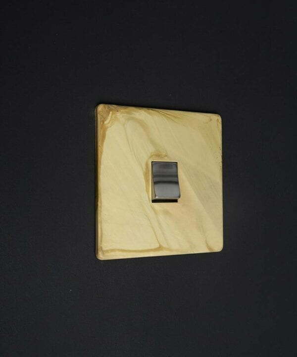 smoked gold single LED rocker switch with matt gold plate and single silver rocker detail against black wall