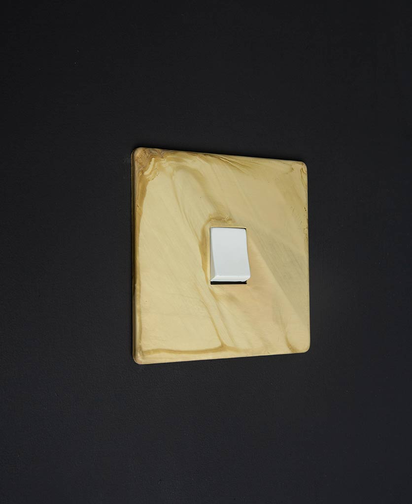 smoked gold single LED rocker switch with matt gold plate and single white rocker detail against black wall