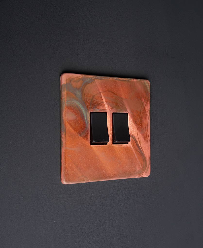 brushed copper light switch with double black rocker detail on black wall