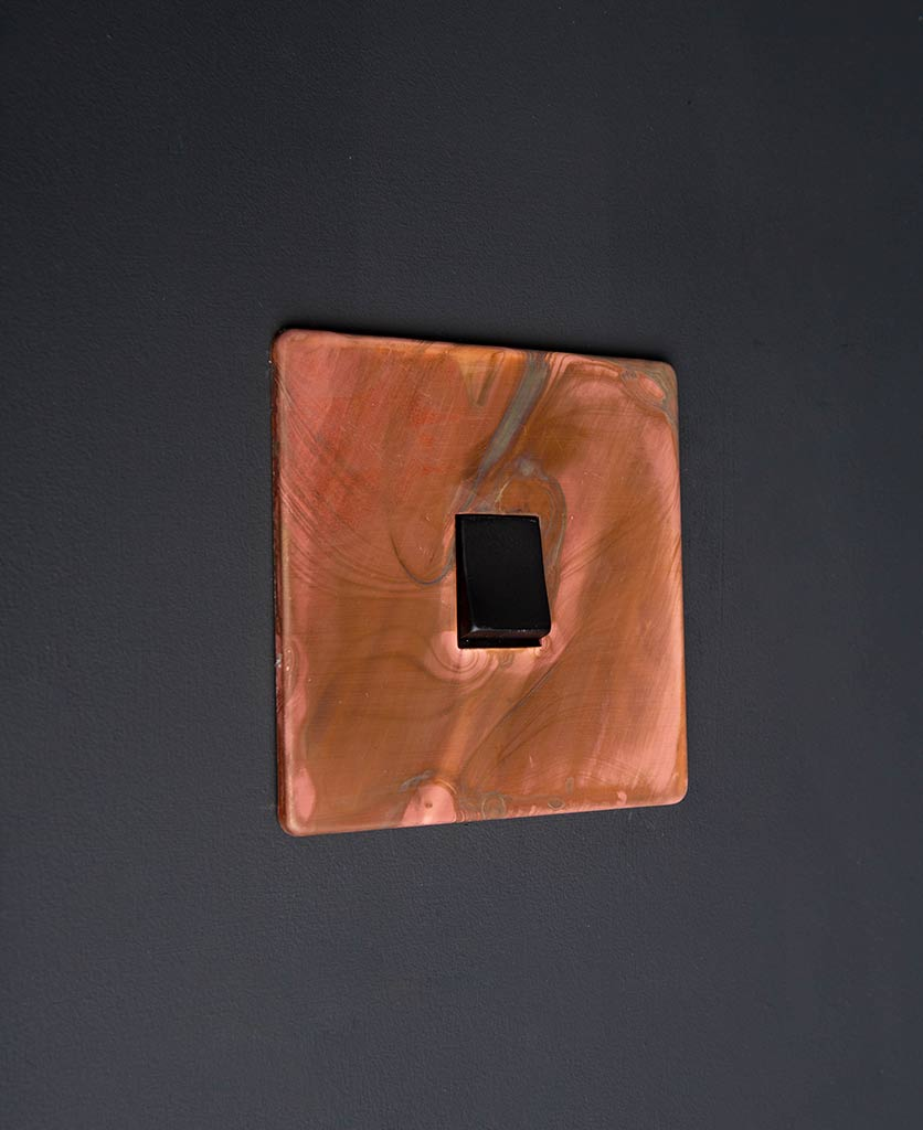 intermediate copper light switch with single black rocker detail on black wall