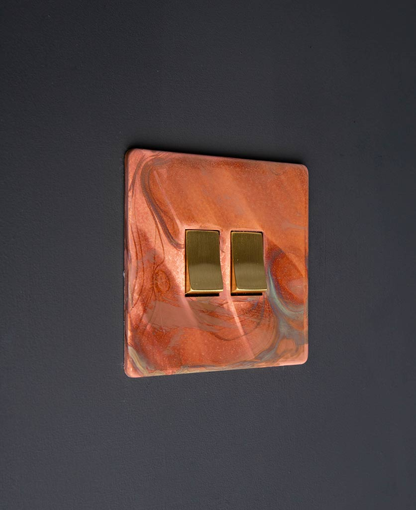 brushed copper light switch with double gold rocker detail on black wall